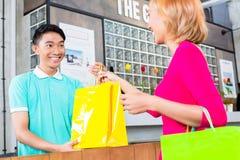 Shoppa assistenten som räcker köpet till kvinnan Arkivbild