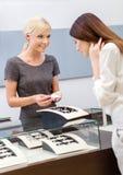 Shoppa assistenthjälpdamen för att välja smycken royaltyfri fotografi