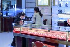 Shoppa assistenthjälpdamen för att välja smycken arkivfoto