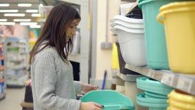 Shoppa av gods för hem En ung kvinna väljer en stor plast- bäcken lager videofilmer