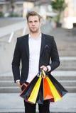 Shoppa bara Folkfyndshopping blir partner med mer liknande medbrottslingar i brott Mannen bär shoppingpåsen Grabb som bara shoppa Royaltyfri Bild