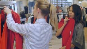 Shoppa den unga kvinnan för assistenthjälp till shoose en klänning i galleria Arkivbilder