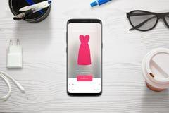 Shoppa direktanslutet med en mobiltelefon Kvinnan väljer format och färg av klänningen med lagret app arkivbild