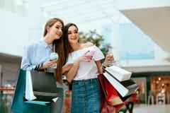shoppa för flickor Kvinnliga vänner i galleria royaltyfria bilder