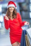 shoppa för jul Attraktiv lycklig flicka med kreditkorten och s Arkivfoton
