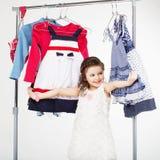 Shoppa för liten flicka och för klädhängare Arkivfoto