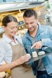 Shoppa för magasinostar för assistenten som den hållande kunden pekar till en dem Arkivbild