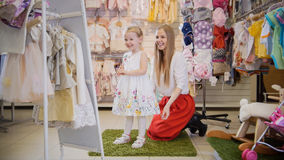 Shoppa för ungar Mamma- och dotterleende i spegeln arkivbilder