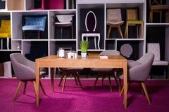 Shoppa försäljningen av möblemang i en köpcentrum Utläggningprövkopia som äter middag trätabellen med textilstolar i grå färger p arkivfoton