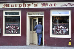 Shoppa gatan, Galway, Irland Juni 2017, stång för Murphy ` s, Man precis Royaltyfri Fotografi