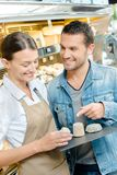 Shoppa hållande magasinostar för assistenten som visar kunden Royaltyfri Bild