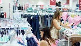 Shoppa i lagret som shoppar avdelning för kläder för barn` s den unga kvinnan, moder väljer saker för hennes barn arkivfilmer