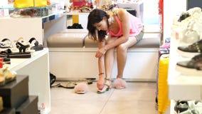 Shoppa i lagret som shoppar i ett skolager försöker en flicka, kvinnasammanträde på soffan, på härliga sandaler variation av stock video