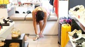 Shoppa i lagret som shoppar i ett skolager försöker en flicka, kvinnasammanträde på soffan, på härliga sandaler variation av arkivfilmer