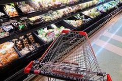 Shoppa i supermarket som finner några nya grönsaker Arkivbild