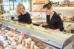 Shoppa kontoristkvinnor på osträknaren i en supermarket arkivbild