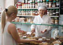 Shoppa kvinnan som erbjuder höga klientmuttrar i lokal konfekt Fotografering för Bildbyråer