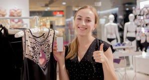 Shoppa, mode, kläder, stil och folkbegrepp Lycklig ung kvinna som ser prislappetiketten i galleria- eller underkläderlagerkopia arkivfoton