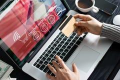 Shoppa online-begrepp Hållande guld- kreditkort för kvinna i hand och online-shopping genom att använda på bärbara datorn hemma fotografering för bildbyråer