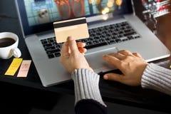 Shoppa online-begrepp Hållande guld- kreditkort för kvinna i hand och online-shopping genom att använda på bärbara datorn hemma royaltyfri foto
