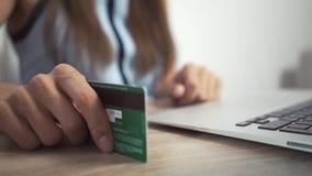 Shoppa online-begrepp Kvinnan r?cker den h?llande kreditkorten och anv?ndab?rbara datorn den kvinnliga handen knackar kortet p arkivfilmer