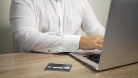 Shoppa online-begrepp Mannen r?cker den h?llande kreditkorten och anv?ndab?rbara datorn kreditkorten  arkivfilmer