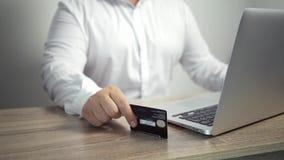 Shoppa online-begrepp Mannen r?cker den h?llande kreditkorten och anv?ndab?rbara datorn den manliga handen knackar kortet p? tabe stock video