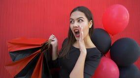 Shoppa på svarta fredag, talar rymmer den lyckliga kvinnlign i hemlighet om stora rabatter och lotten av shopping stock video