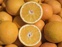 Shoppa räknaren med massor av guld- mogna apelsiner i naturligt ljus Arkivbild