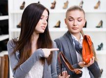 Shoppa stilfulla skor för assistenterbjudanden för kunden royaltyfri fotografi