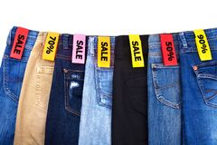 Shoppa upp f?rs?ljningen av kl?der, jeans av bl?a olika f?rger, gr?nt, svart p? vit bakgrund isolerat slut royaltyfri foto