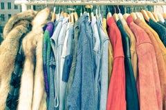 Shoppar begagnad kläder för tappning som hänger på, kuggen på loppmarknaden Royaltyfria Foton