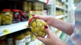 Shoppar caucasian kvinnahänder för Closeup nära hyllor som väljer gröna oliv för marinaden i livsmedelsbutikmarknad arkivfilmer