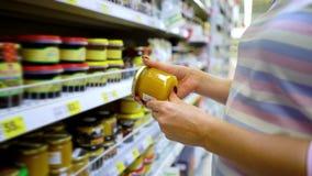 Shoppar caucasian kvinnahänder för Closeup nära hyllor som väljer ljus honung i livsmedelsbutikmarknad lager videofilmer