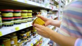 Shoppar caucasian kvinnahänder för Closeup nära hyllor som väljer ljus honung i livsmedelsbutikmarknad stock video