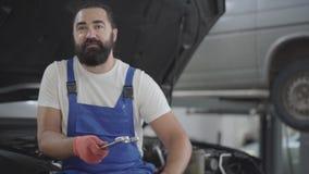 Shoppar den attraktiva skäggiga mekanikern för ståenden som poserar med skruvnyckeln som sitter på huven av en bruten bil i en bi lager videofilmer