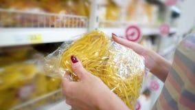 Shoppar den caucasian kvinnan för closeupen nära hyllor och väljapasta i livsmedelsbutikmarknad arkivfilmer
