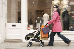 Shoppar den driftiga sittvagnen för modern vid kläder Arkivfoto