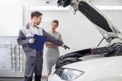 Shoppar den förklarande bilmotorn för den unga manliga repairmanen till den kvinnliga kunden i bilreparation Royaltyfri Bild