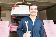 Shoppar den hållande skruvnyckeln för arbetaren mot bilelevator i auto arkivbilder