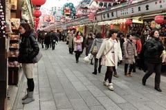 Shoppar fodra banan till den Sensoji templet fylls med ferieshoppare för nya år Royaltyfri Foto