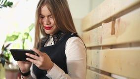 Shoppar inkommande post för unga och nätta kvinnakontroller på mobiltelefonen i coffe stock video