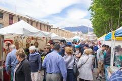 Shoppare bläddrar stallsna på de Salamanca marknaderna Arkivbild