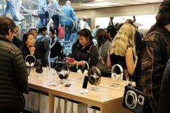 Shoppare och medlemmar av allmänheten som ses i en välkänd detaljist, en försökande hörlurar och annan släkt tillbehör royaltyfri bild