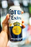 Shoppare r?cker att rymma a kan av Corona Extra m?rkes?l royaltyfri foto