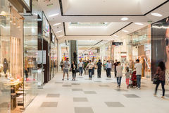 Shoppare rusar i lyxig shoppinggalleriainre Arkivbild