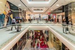 Shoppare rusar i lyxig shoppinggalleriainre Arkivfoton