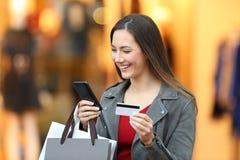 Shoppare som betalar på linje med kreditkorten i en galleria royaltyfria bilder