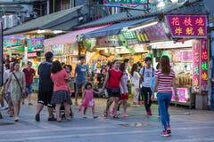 Shoppare som går förbi diversehandel på den Danshui flodstranden som shoppar område Royaltyfria Foton