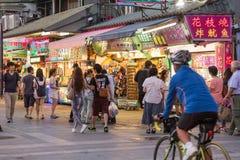Shoppare som går förbi diversehandel på den Danshui flodstranden som shoppar område Arkivfoton